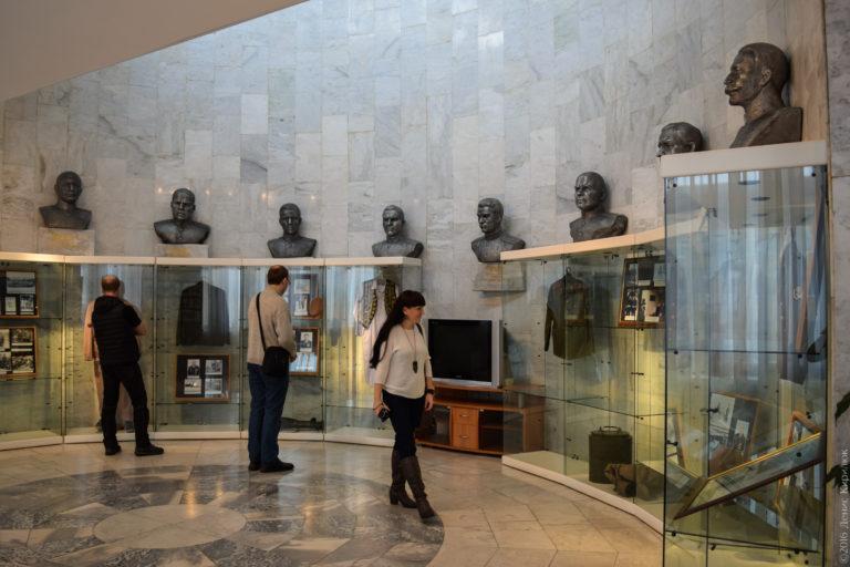 Полукруглый зал, отделанный серым мрамором, с бюстами, закрепленными на стене.