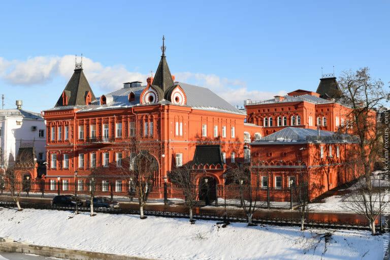 Большой комплекс 2- и 3-этажных строений с красными стенами и чёрной крышей с шатровыми элементами.