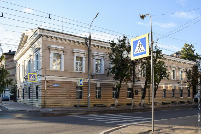 Двухэтажное здание в стиле классицизм, коричневого цвета.