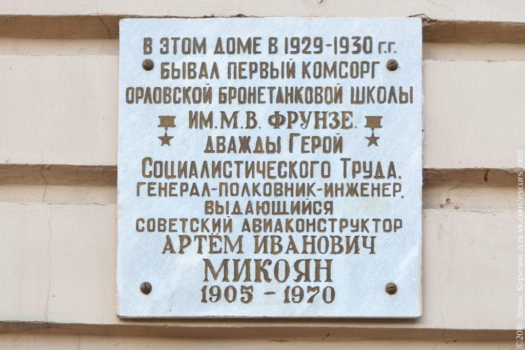 Светлая мемориальная доска с темными буквами и изображением двух звезд героя.