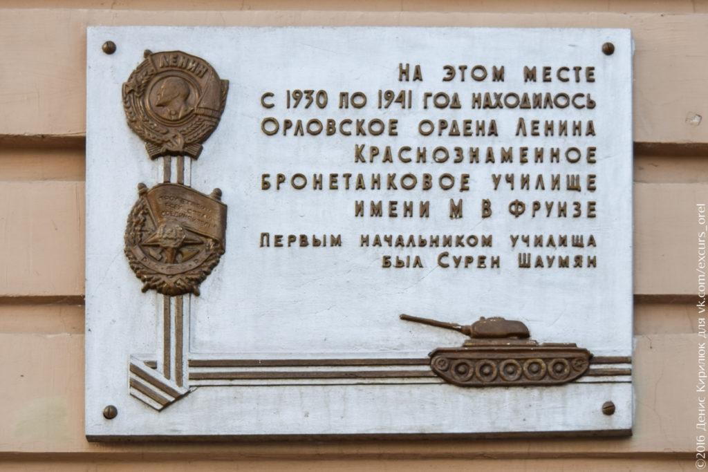 Светлая доска с изображением орденов, танка и георгиевской ленты.