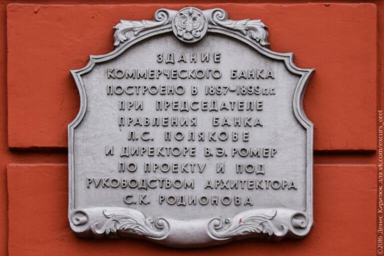 Стилизованная мемориальная доска с двуглавым орлом и надписью «Здание коммерческого банка построено в 1897-1899 гг. при председателе правления банка Л.С. Полякове и директоре В.Э. Ромер по проекту и под руководством архитектора С.К. Родионова».