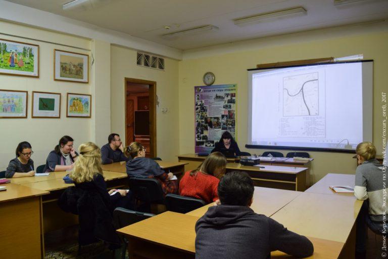 Учебная аудитория с рисунками на стенах, на экране - старая карта Орла.