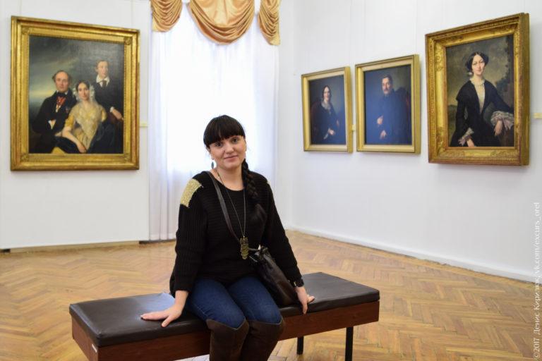 Девушка среди картин в музее.