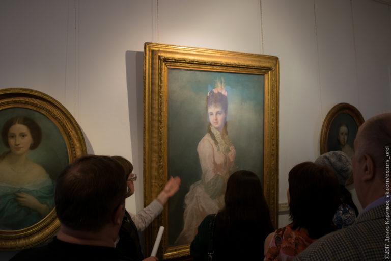 Экскурсанты изучают портреты дворянок в музее.