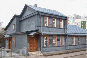 Деревянный дом со вторым этажом, серыми стенами и оранжевыми наличниками.