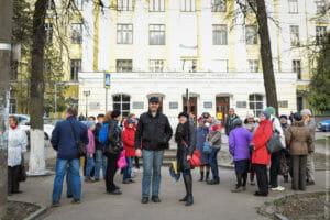 Группа людей на фоне здания с неоклассическом стиле.