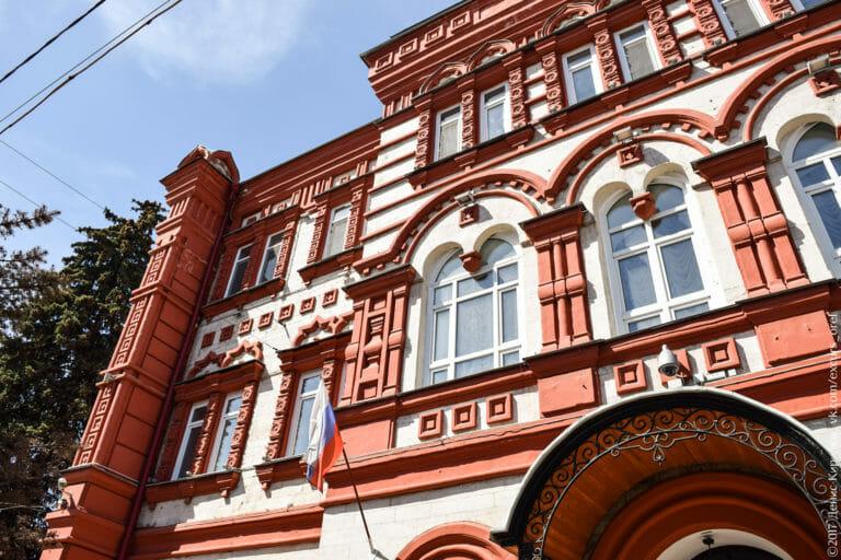 Богато декорированный фасад в неорусском стиле: каменная резьба, наличники, стилизованные кокошники, сдвоенные арки, гирьки.