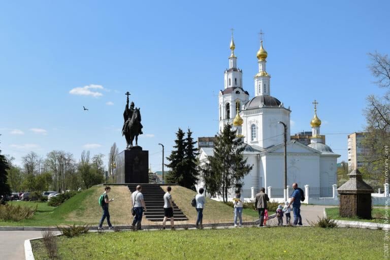 Конный памятник царю с крестом в руке на фоне белого храма с чёрными куполами и золотыми главками.