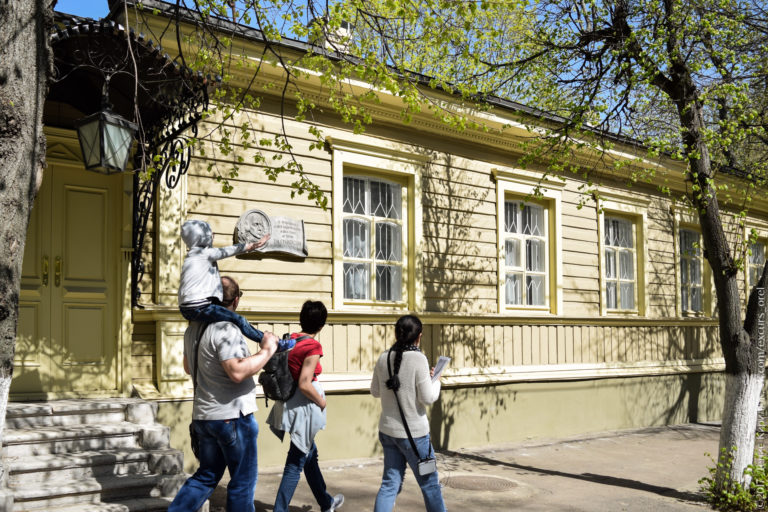 Экскурсанты на фоне деревянного дома с мемориальной доской с барельефом.