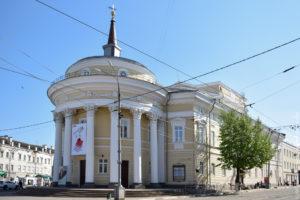 Здание в классическом стиле с полуротондой и шпилем, а также с театральными масками на фасаде.