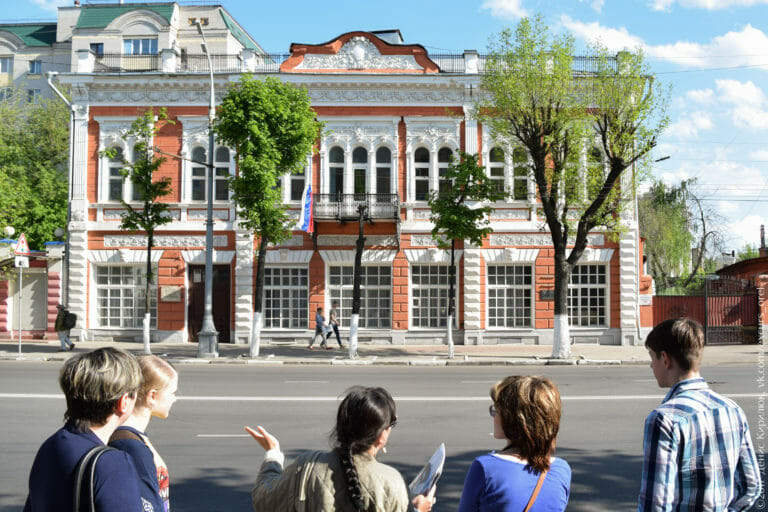 Двухэтажный кирпичный дом, красно-белый, богато украшенный лепниной.