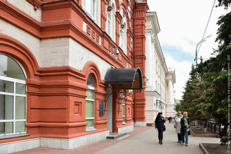 На переднем плане здание в русском стиле, за ним – в классическом, с колоннами и портиком.