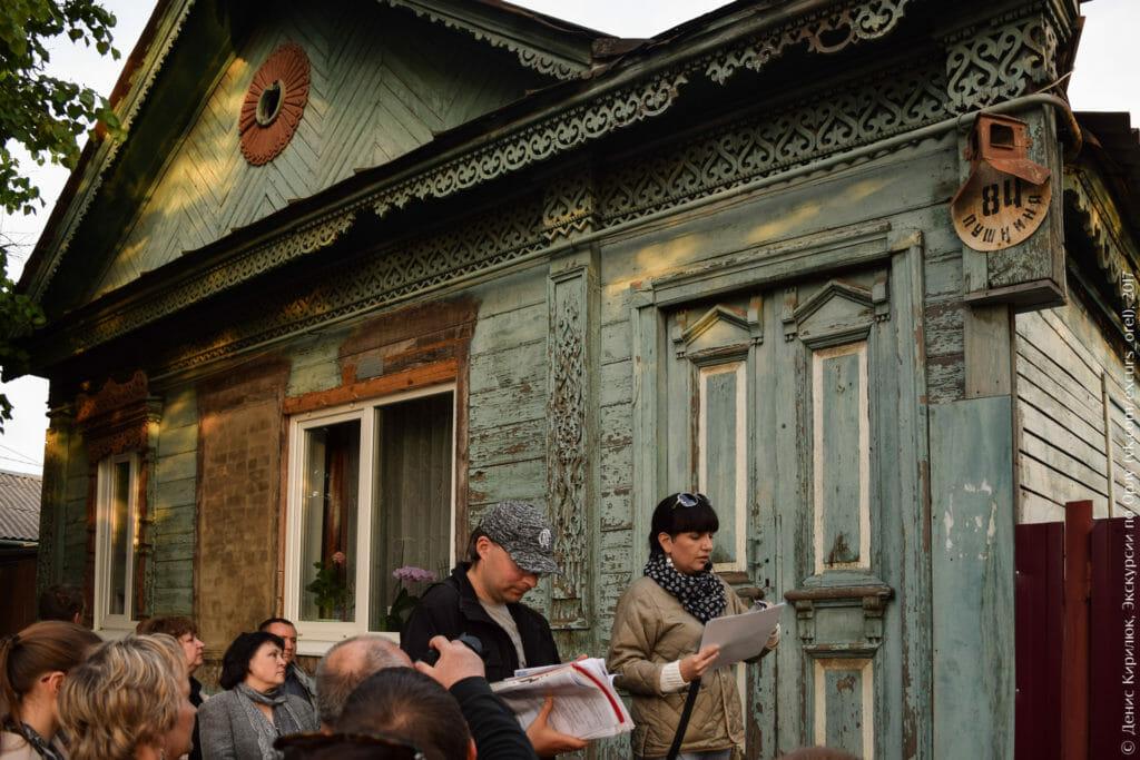 Старый деревянный дом с красивой резьбой и грубо вставленными пластиковыми окнами.
