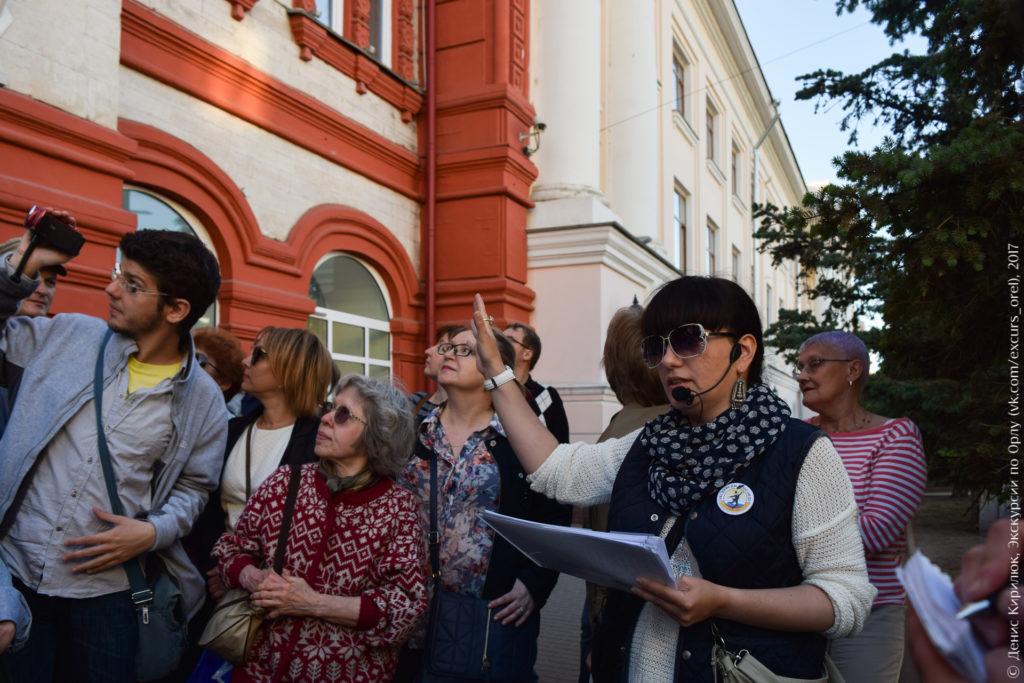 Экскурсанты на фоне здания в неорусском стиле.