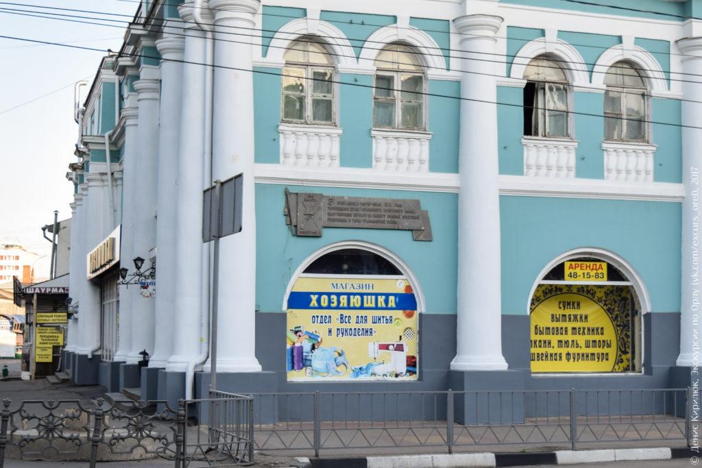 Здание в классическом стиле с мемориальной доской в виде знамени.