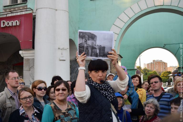 Экскурсовод показывает фото военного времени.