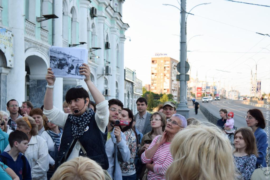 Экскурсия на фоне здания гостиного двора и моста.