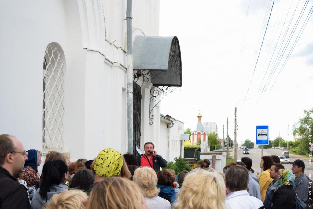 Люди под стенами церкви на фоне часовни.