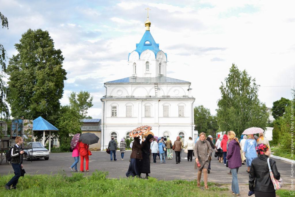 Белый храм с синим шатровым куполом и золотой главкой.