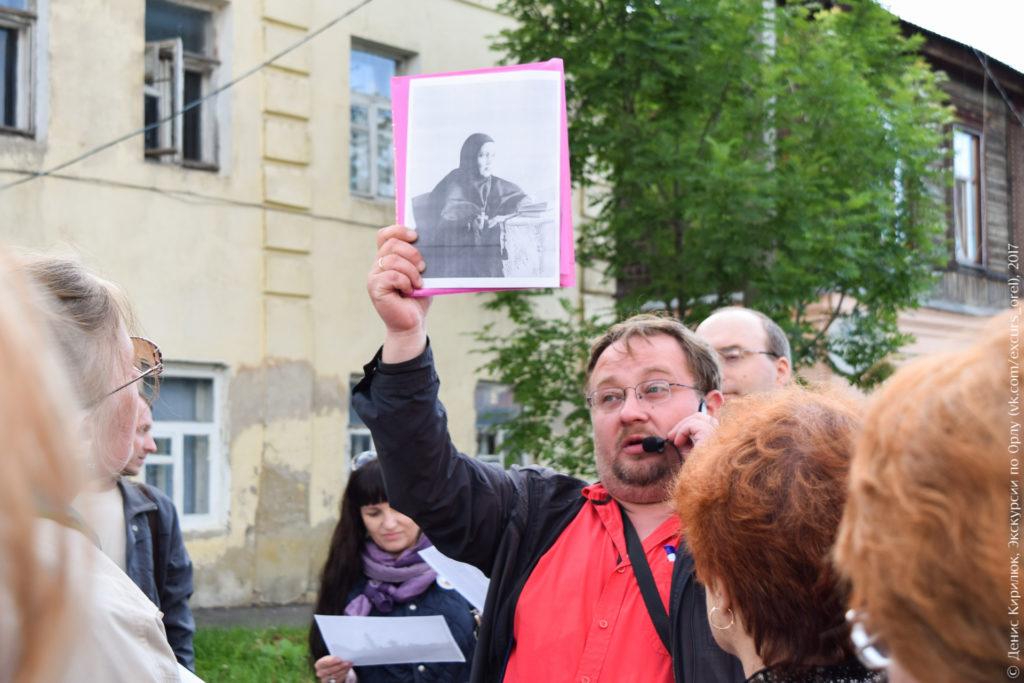 Экскурсовод показывает старое фото монахини.