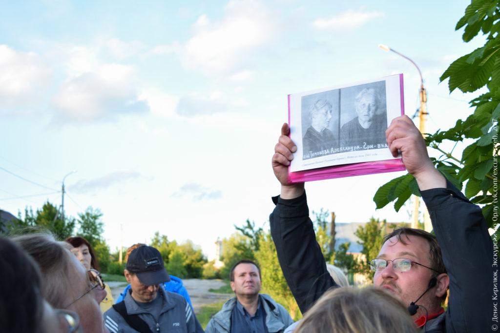 Экскурсовод показывает фото репрессированной женщины.