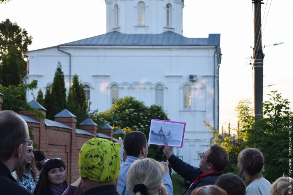 Экскурсовод показывает старое фото на фоне церкви.