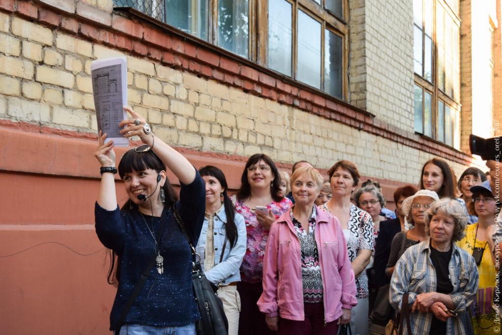 Экскурсанты на фоне советского производственного здания.