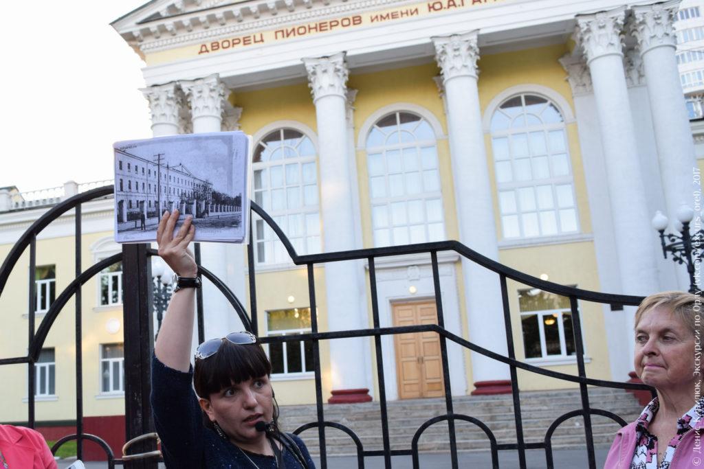 Экскурсовод на фоне дворца пионеров в стиле «сталинский ампир».