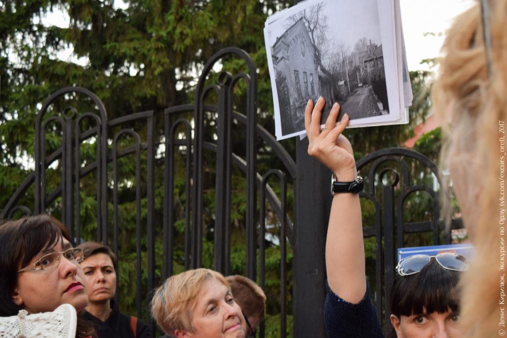 Экскурсовод показывает фото несохранившегося дома причта.