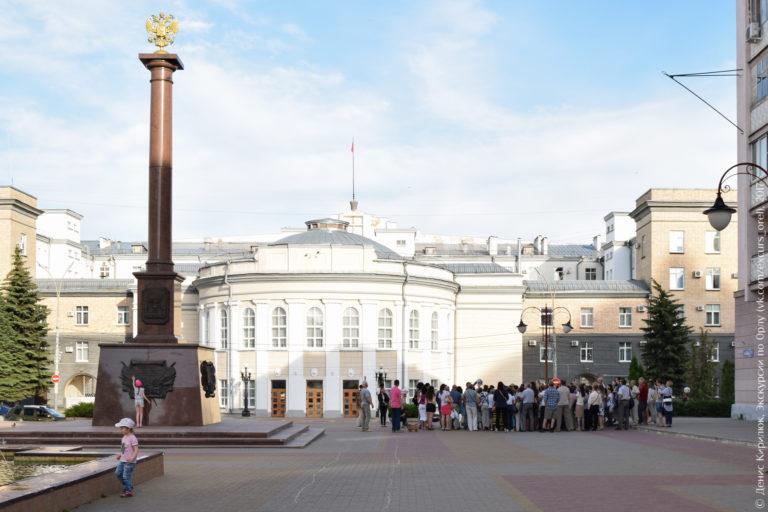 Коричневая стела с золотым двуглавым орлом на вершине на фоне полукруглого здания.