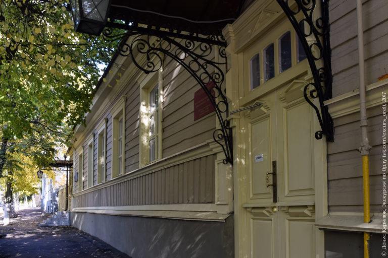 Деревянный дом в стиле классицизм, резная дверь с металлическим козырьком.