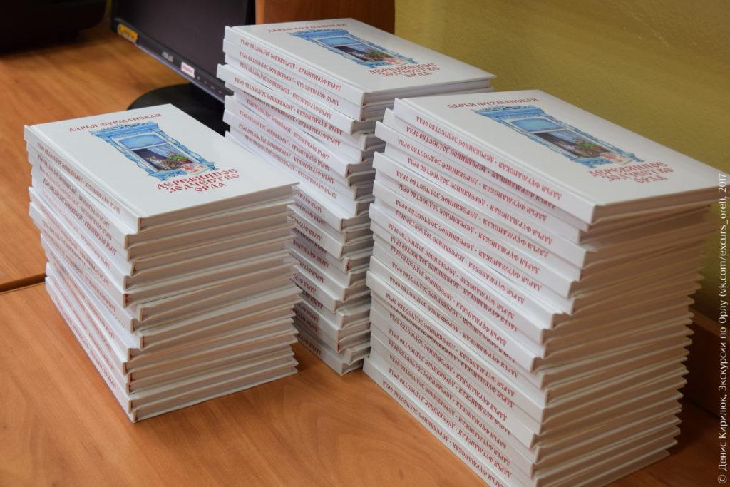 Экземпляры книги, уложенные друг на друга. Книги белые с нарисованным синим наличником на обложке.