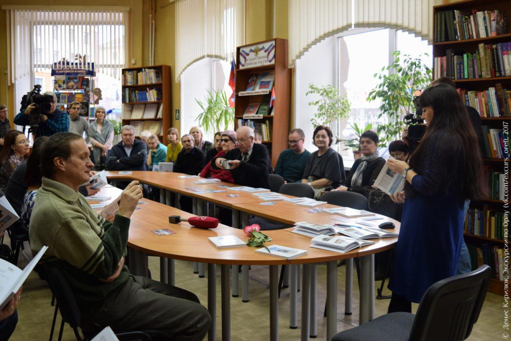 Люди сидят вокруг овального стола и слушают автора книги