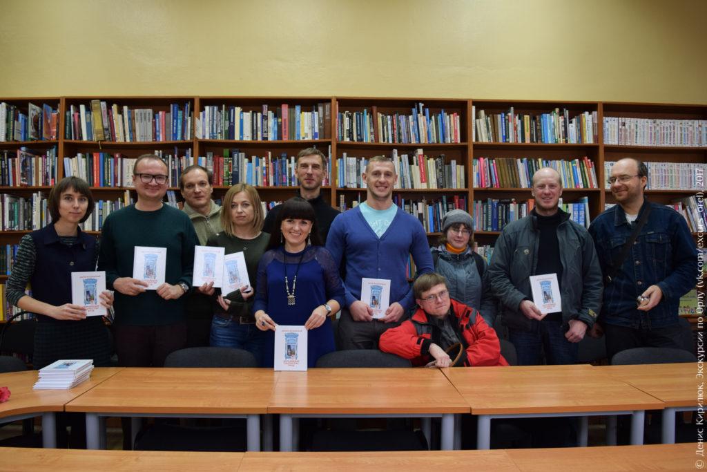 Группа людей на фоне книжных стеллажей и экземплярами книги «Деревянное зодчество Орла» в руках
