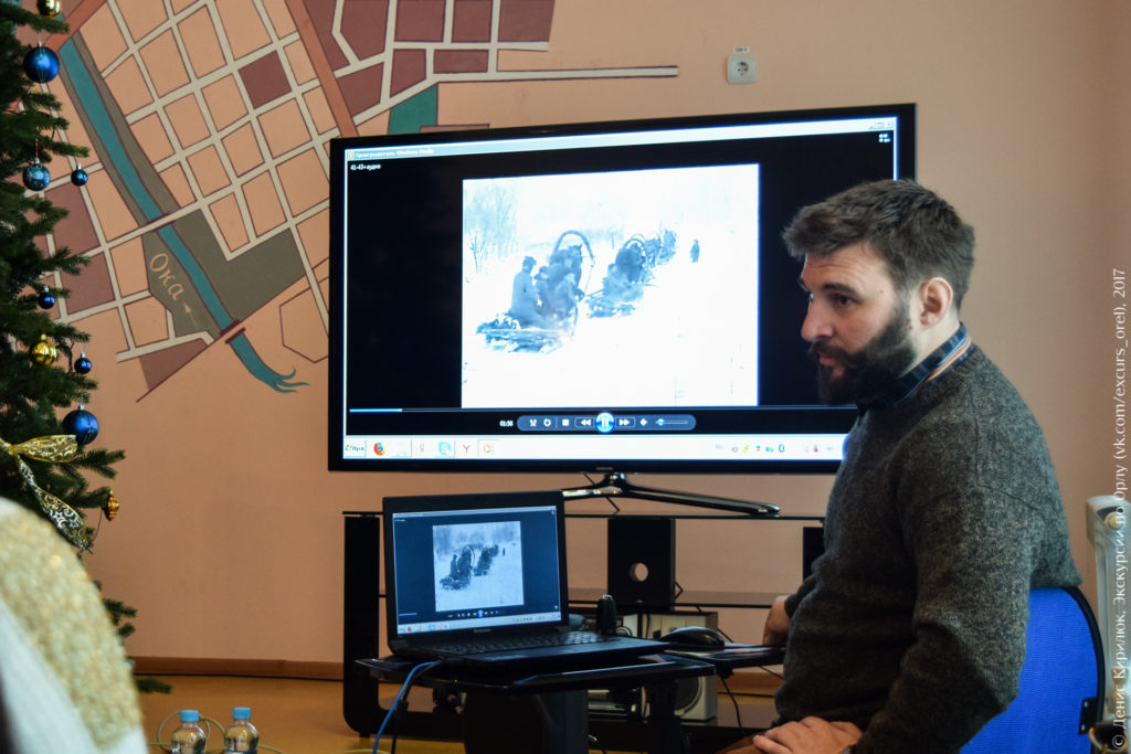 Лектор показывает на большом экране старые фотографии.