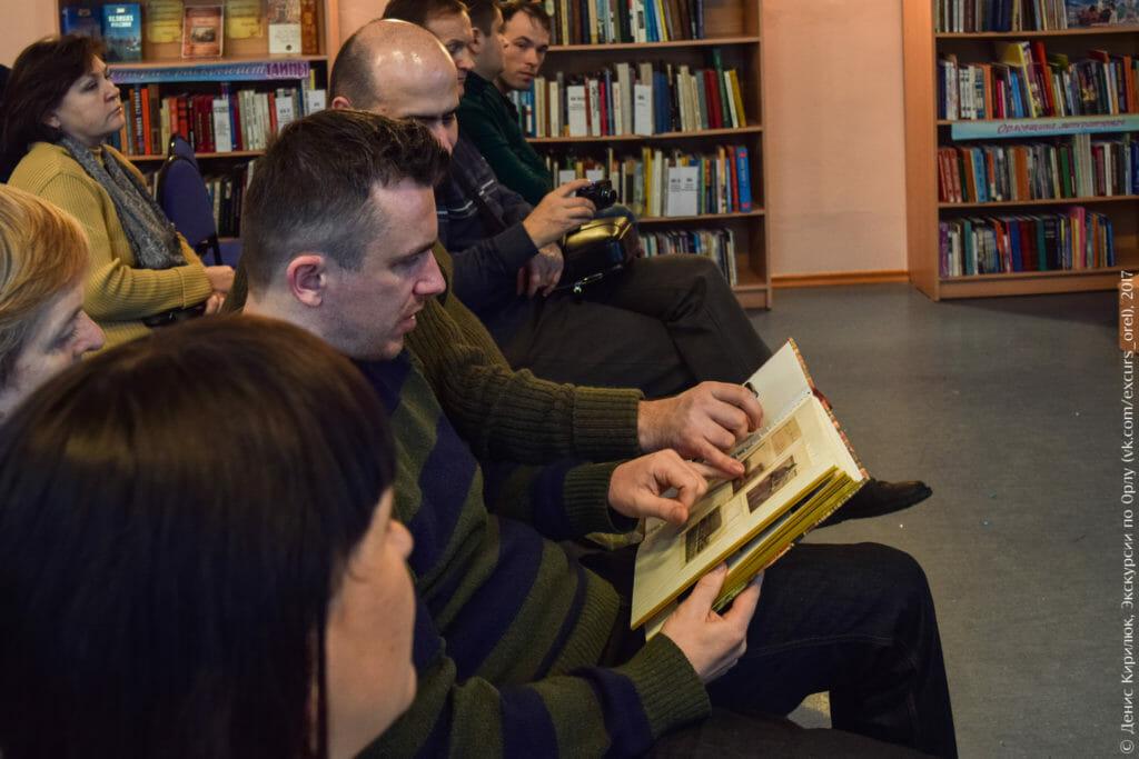Люди изучают содержимое фотоальбома.