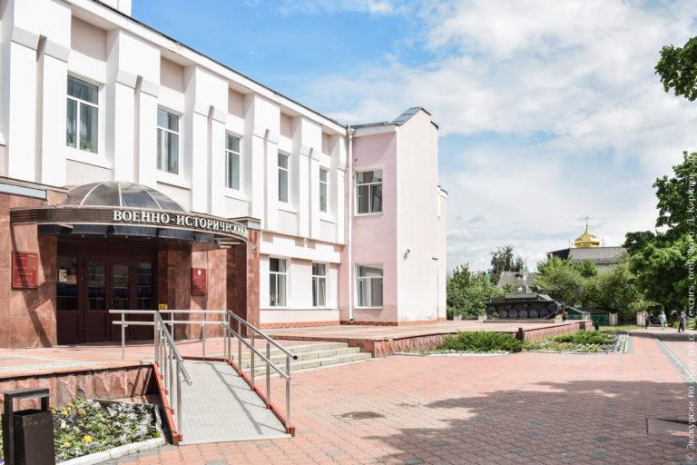 Двухэтажное розовое здание, перед ним - танк Т-70.