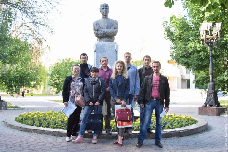 Группа людей с сертификатами на фоне памятника Есенину в Орле.