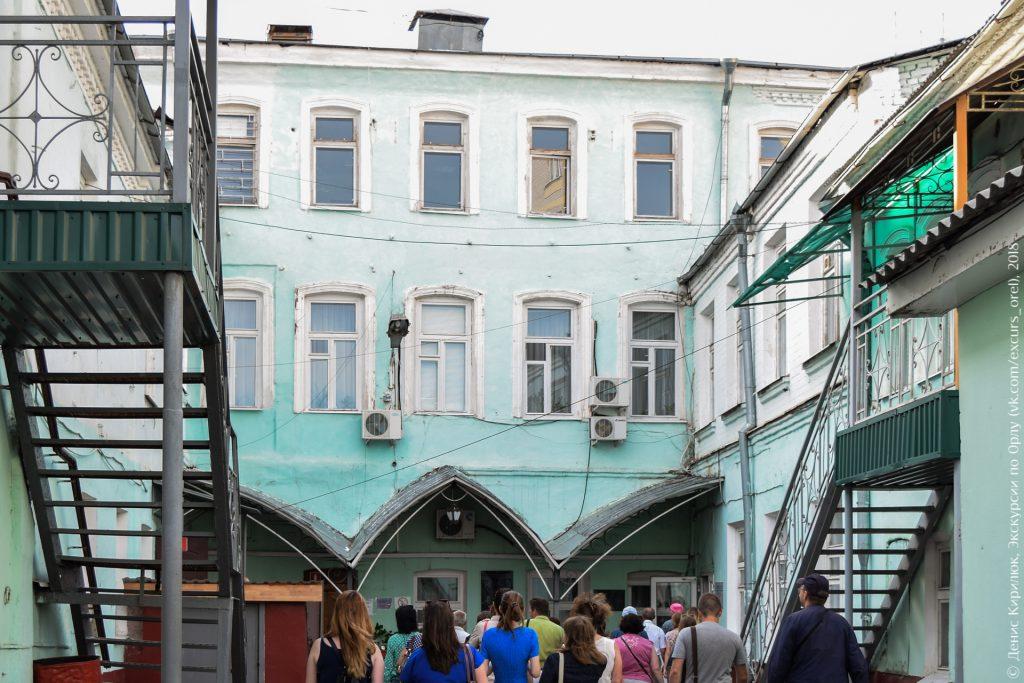 Дворовая часть старого трехэтажного дома с арочными окнами