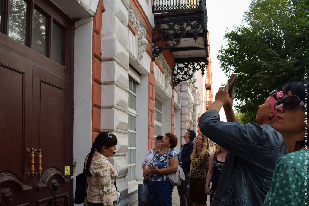 Экскурсанты фотографируют красивый старый дом