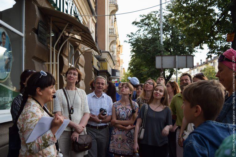 Экскурсанты на фоне высокой сталинки с декоративными балконами