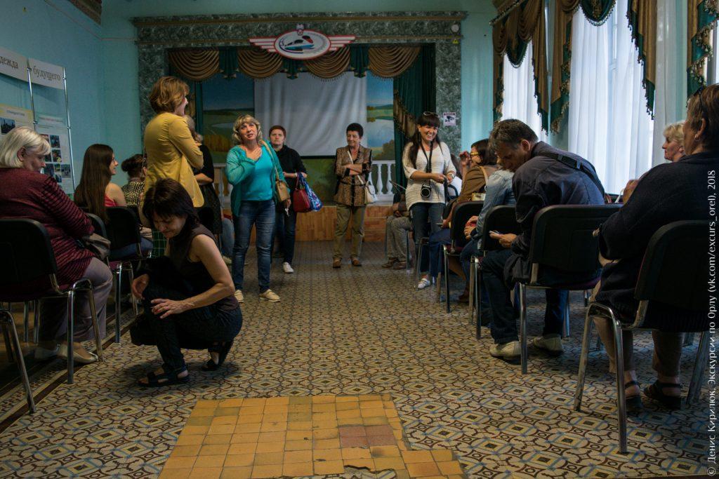 Экскурсанты изучают плитку на полу