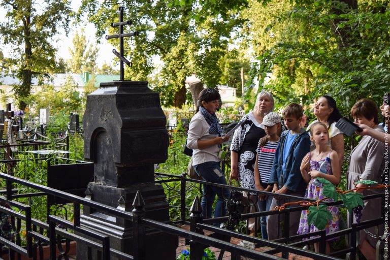 Экскурсовод и старое надгробие с крестом
