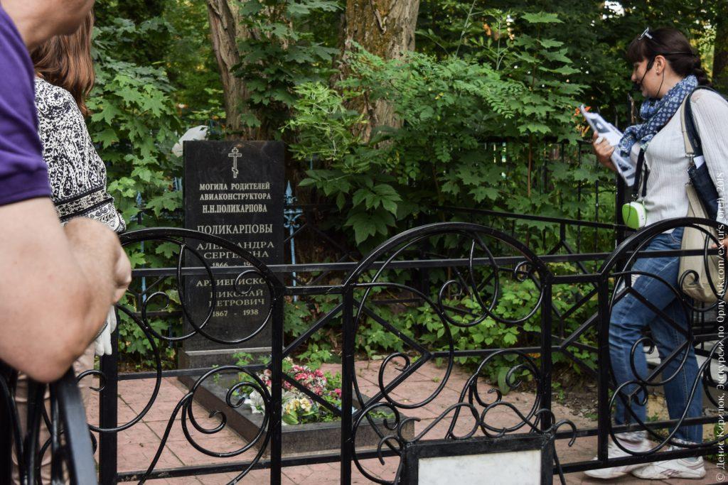 Чёрное прямоугольное надгробие за оградой