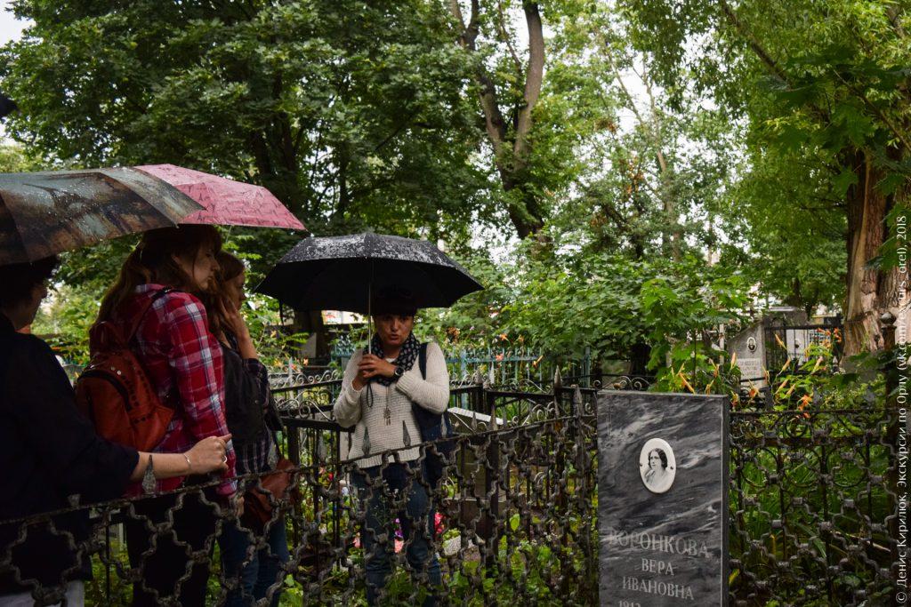 Люди на кладбище под зонтами, много зелени