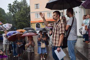 Экскурсовод ведёт экскурсию под дождём
