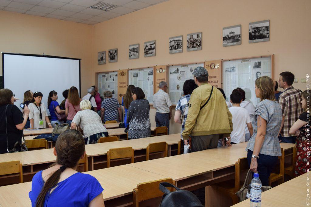 Люди стоят в учебном классе с партами