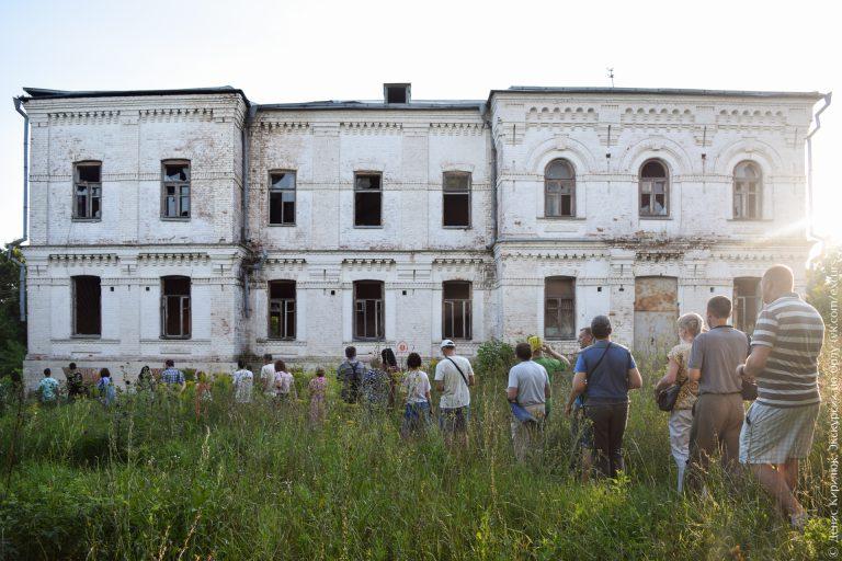 Заброшенный двухэтажный каменный дом с пустыми арочными окнами
