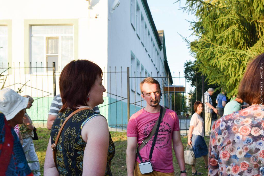 Экскурсанты на фоне двухэтажного здания